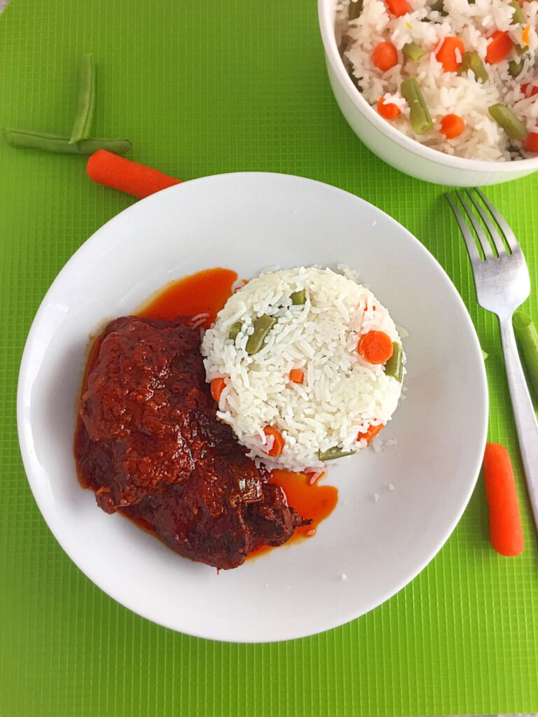 Vegetable rice, served in a white plate with African red Stew