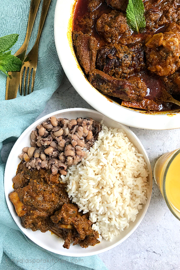 Ofe Akwu | Palm nut Soup served with white rice and black eyed peas with a glass of orange juice by the side