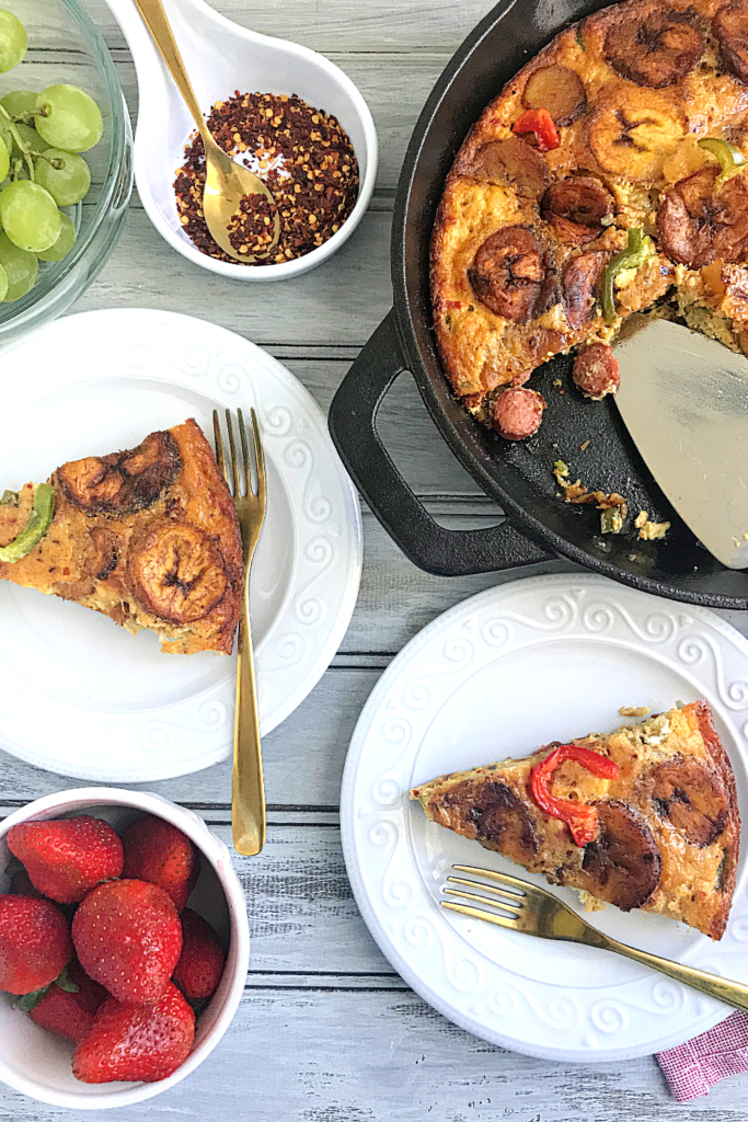 Plantain frittata served from cast iron skillet strawberries and grapes on the side. peppers flakes on the table for garnishing