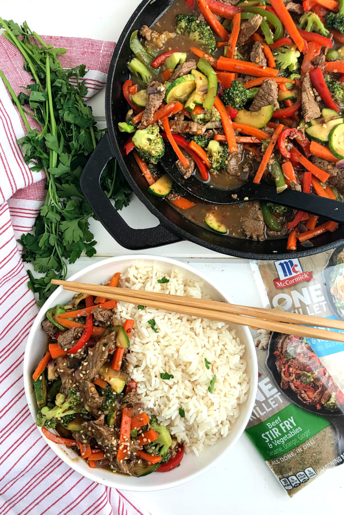 Beef Stir fry and vegetables in a skillet, some beef stir fry served over white rice on the side