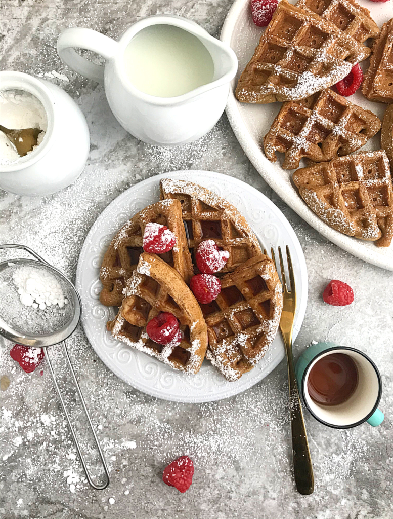 Gingerbread waffles served in a plate, topped with raspberries, powdered sugar and a drizzle of syrup from a cup