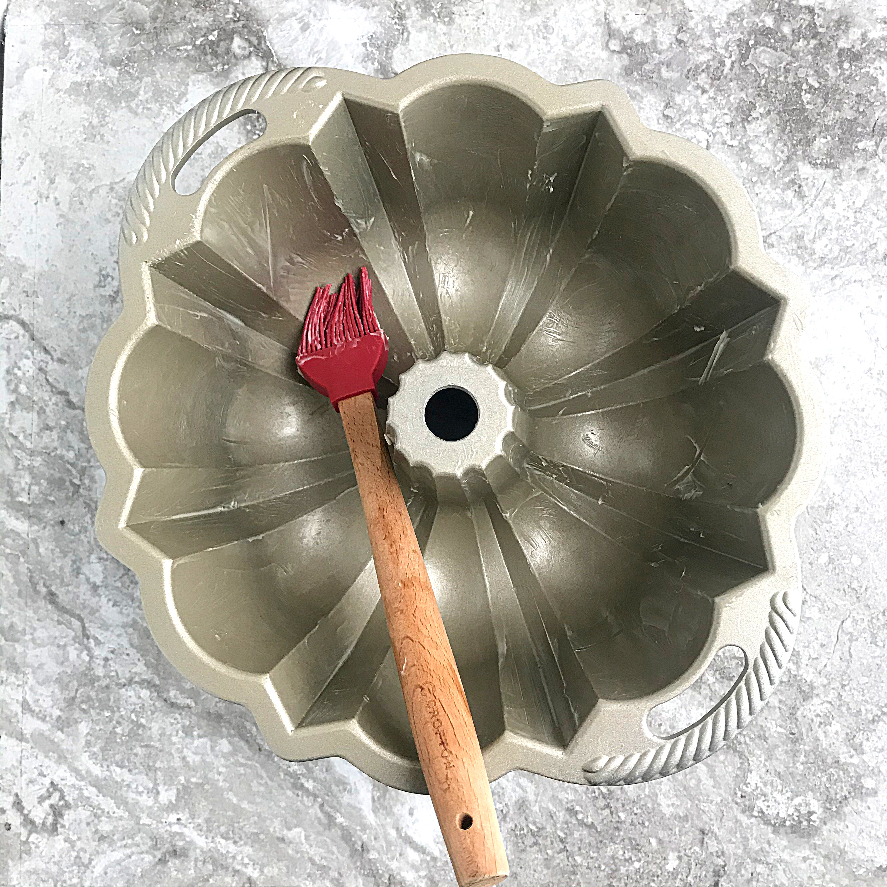 applying butter to a bundt pan with s red bristled pastry brush. first step on how to grease a bundt pan,