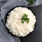 cooked basmati rice in a black bowl with parsley leaves on top