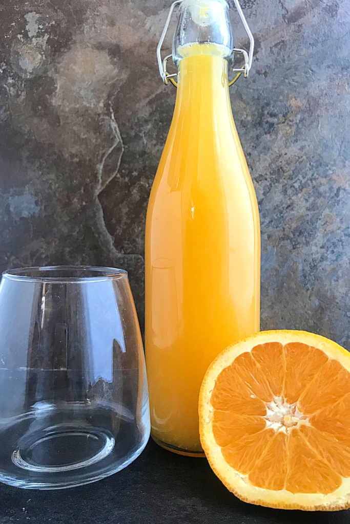 a bottle of homemade orange juice with an empty glass by the side and half an orange on the other side