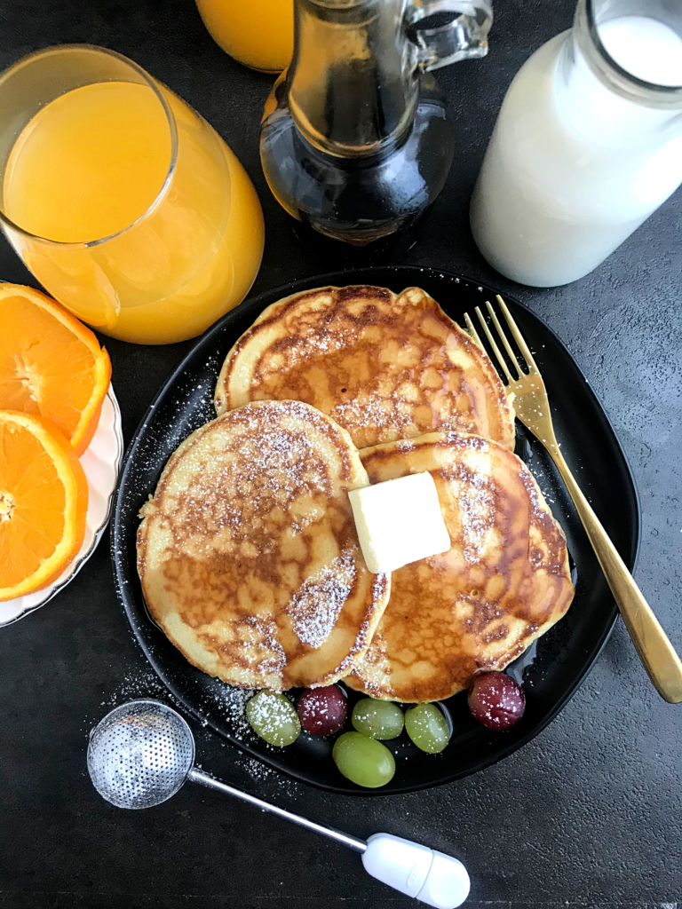 A centered plate of pancakes, topped with butter and a side of grapes, surrounded by a glass of juice, slices of orange, a bottle of maple syrup and a bottle of milk