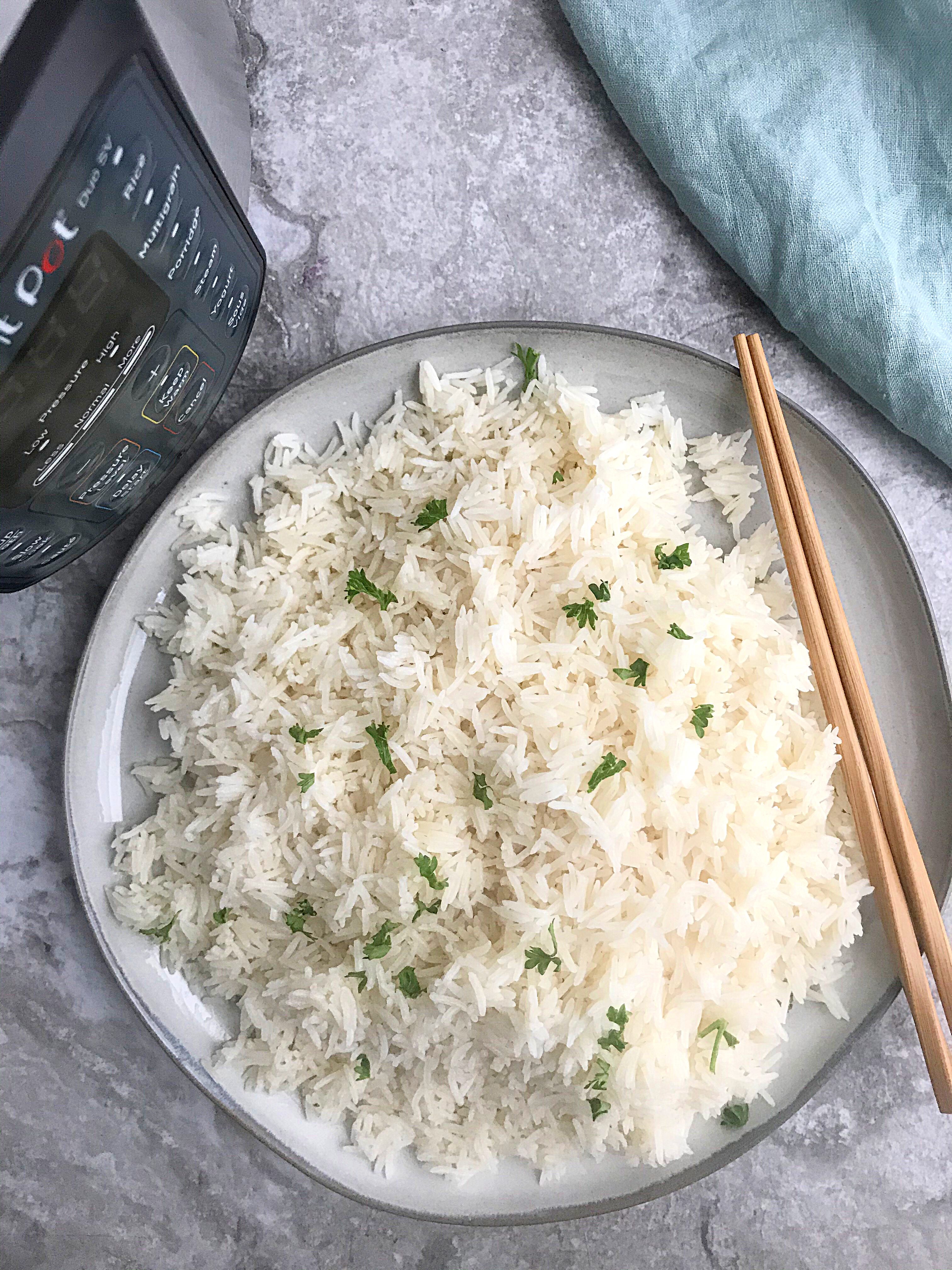 A plate of basmati rice with chopsticks on top and an instant pot at the top left corner