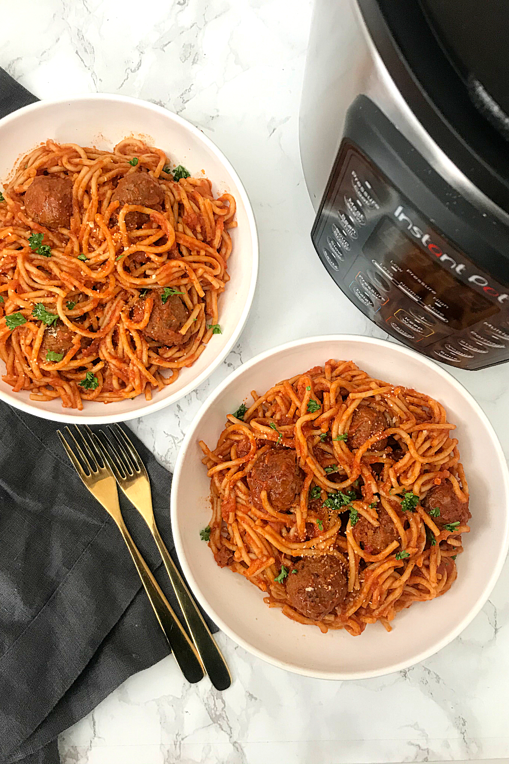 Instant Pot Spaghetti and meatballs served in two white pasta bowls, with 2 golden forks on the left side and an instant pot on the right