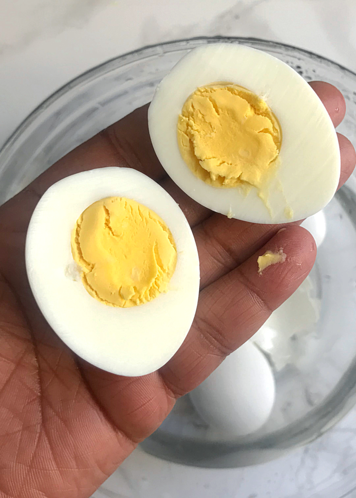 a close shot of a hand holing a boiled egg sliced in two