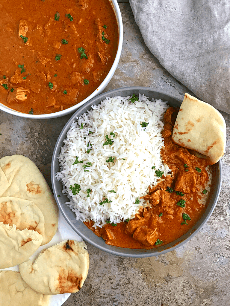 some nan bread in a plate with another dipped in a plate of rice and chicken tikka masala