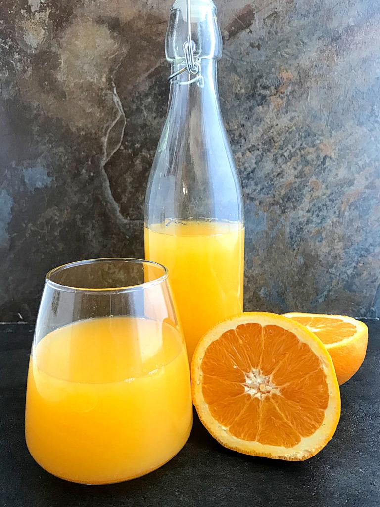 Orange juice in a swing bottle, a glass cup, an orange fruit sliced in half