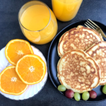 Orange juice in a glass cup, orange slices in a white plate.Pancakes in a black plate