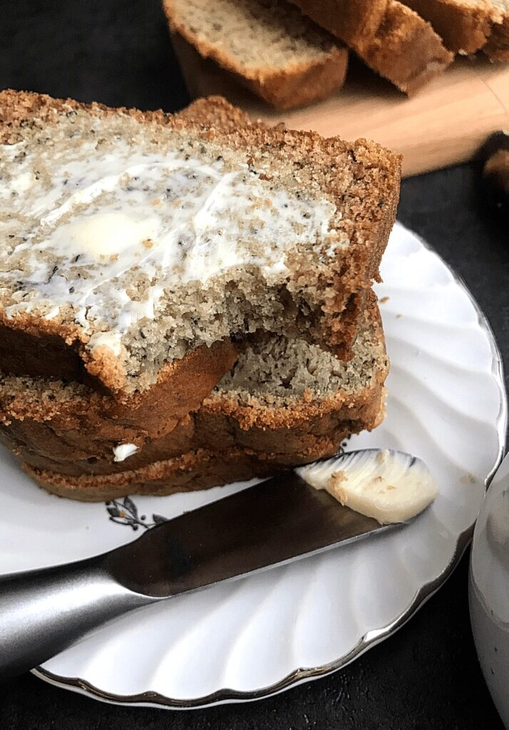 3 slices of banana bread stacked on a white plate, some butter on a butter knife,
