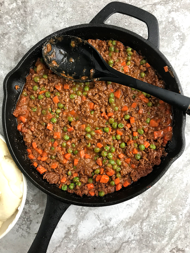 a cast iron skillet filled ground beef filling for making Cottage pie