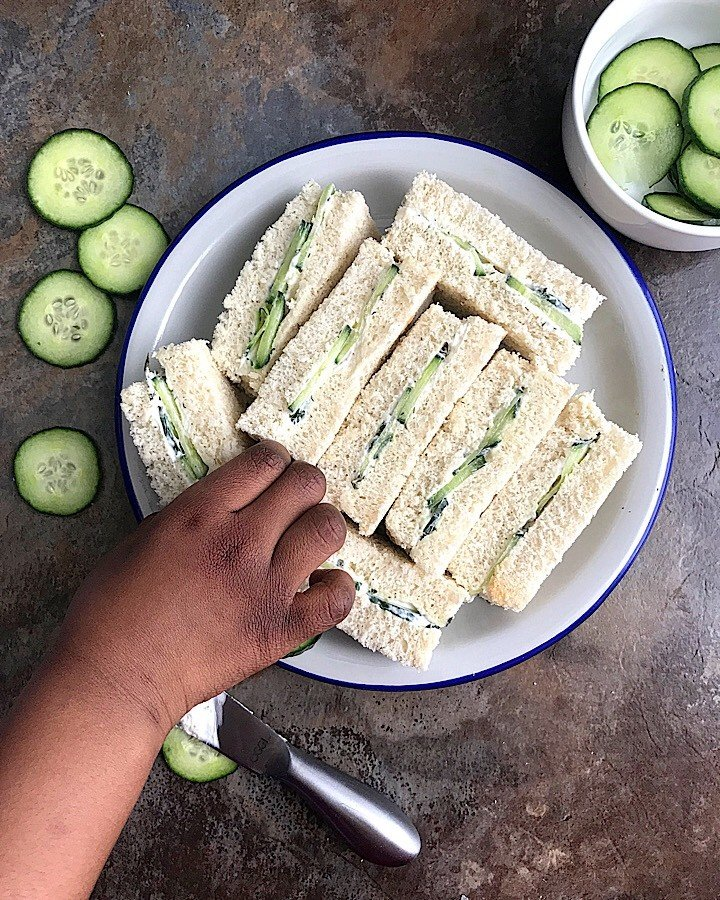 A plate of Cucumber Sandwiches, with a child's hand over it, cucumber slices lying around and in a white bowl