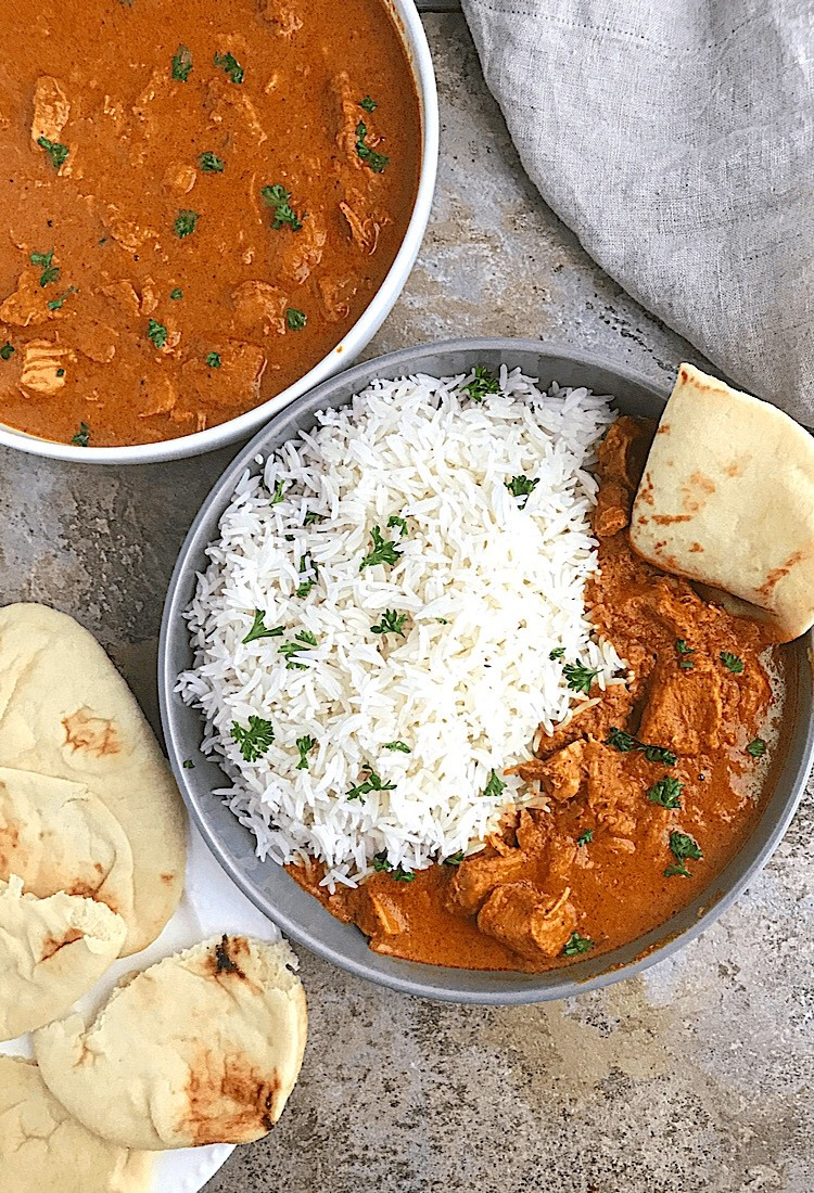 Instant Pot Basmati Rice served in a grey plate with tikka masala, another white plate of tikka and some naan bread