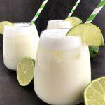 3 glasses of brazilian lemonade with halves of lime fruit around it.