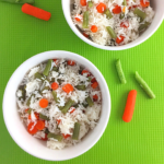 vegetable rice in two white bowls, some carrots and string beans in the background