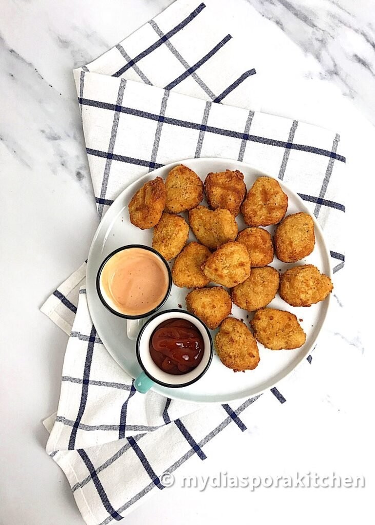 Air fried frozen  chicken nuggets in a white plate with two dips in two small mugs